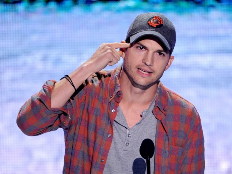 Ashton Kutcher in a Chicago Bears baseball cap and plaid shirt speaks into a microphone and points at his head