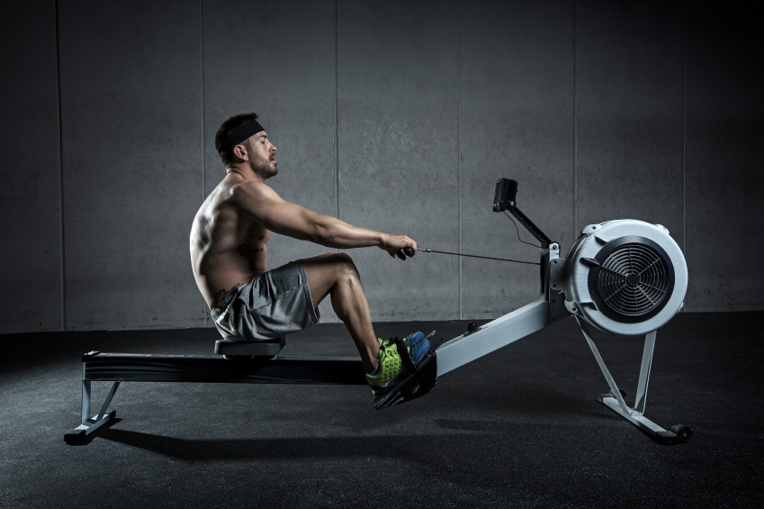 man doing cardio on rowing machine