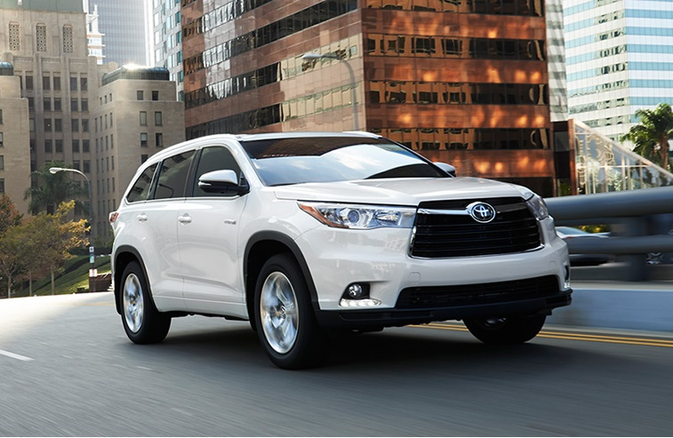 A white 2015 Toyota Highlander Hybrid on a city road
