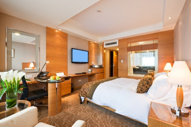 Luxury hotel room with furniture and flat screen TV.