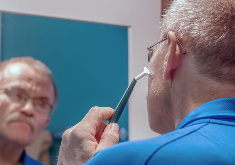 A man shaves his face.