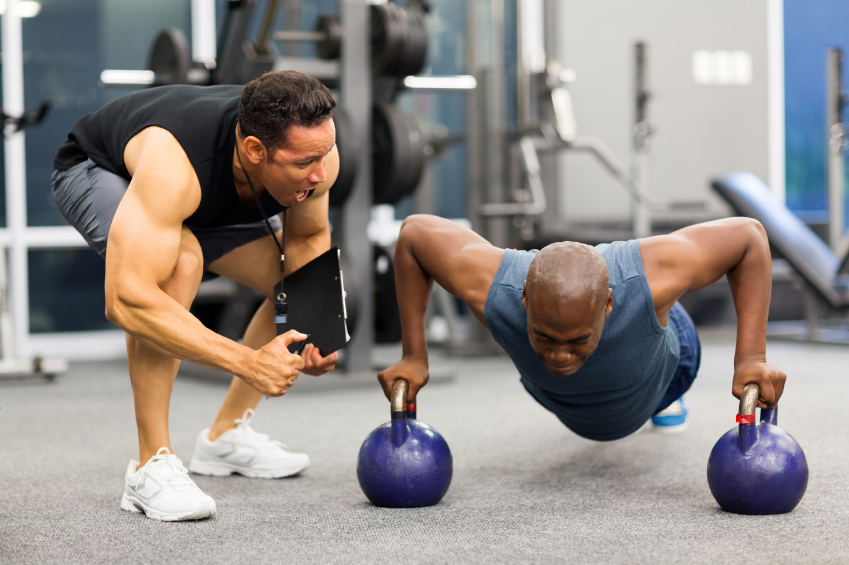Personal trainer encouraging man to do push-ups