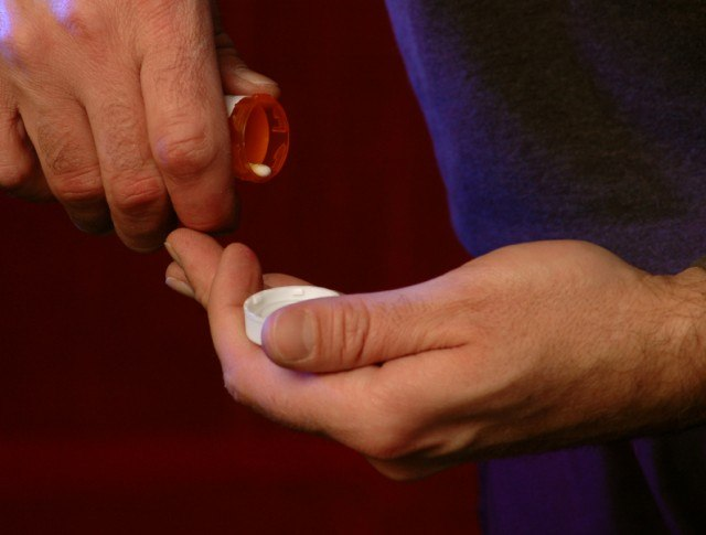 man pouring pills into his hand