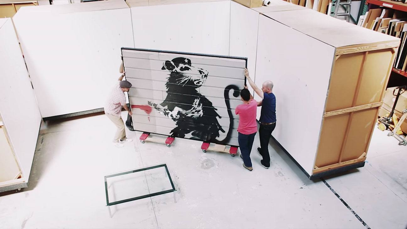 Two men wheel a piece of graffiti art in an art installation