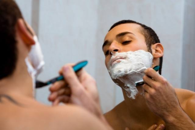 man shaving with razor and shave cream