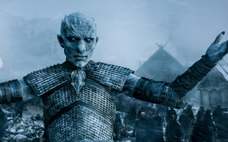 The Night King stands in the snow with his arms stretched out.