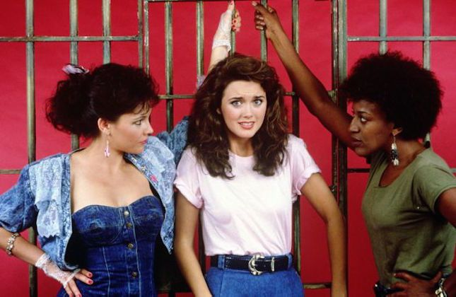 The cast of Women in Prison, posing for a promo photo in front of prison abrs and a red background