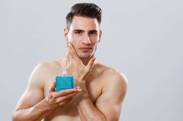 Man holding aftershave while touching his face