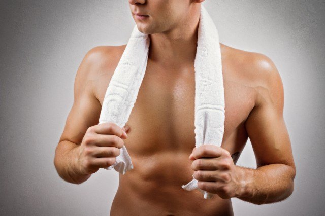 Man holding towel around neck for workout