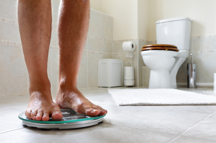 a man stepping on a scale in his bathroom