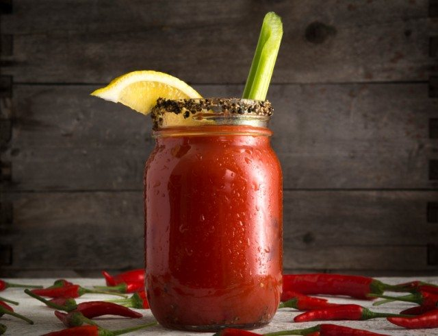bloody mary garnished with a peppercorn rim, lemon, and a celery stalk