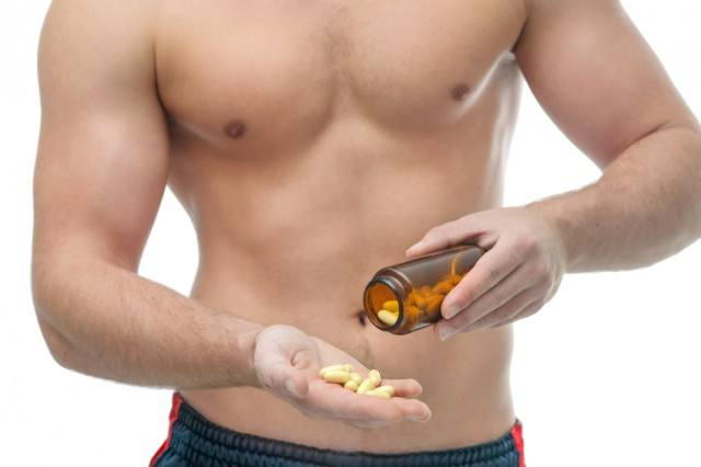 A man taking vitamins or supplements behind a white background.