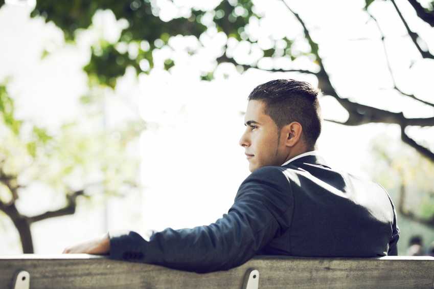 a handsome man sitting on a bench