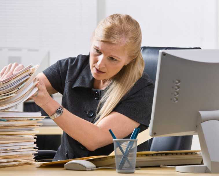 a woman looking through a stack of papers
