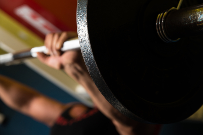 man lifting a barbell for bigger triceps