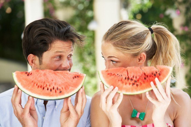 a couple hanging out while eating watermelon