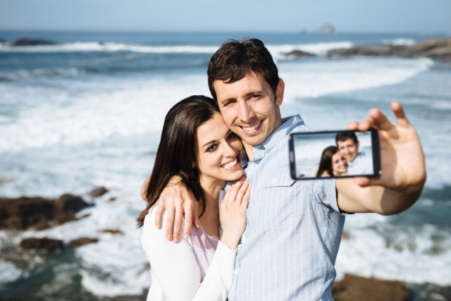 A couple takes a selfie at the beach with a phone.
