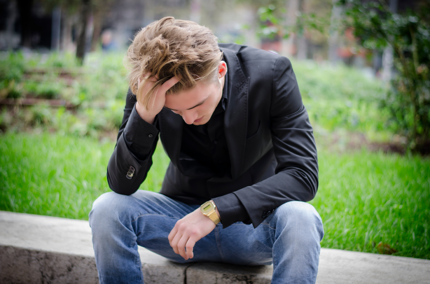 A sad man sitting outside by himself