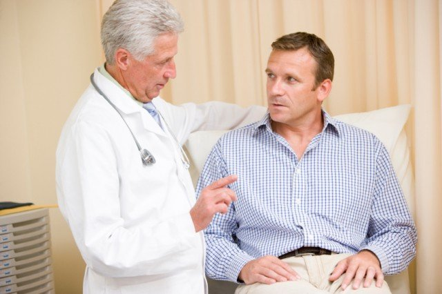 doctor talking to a male patient in an exam room