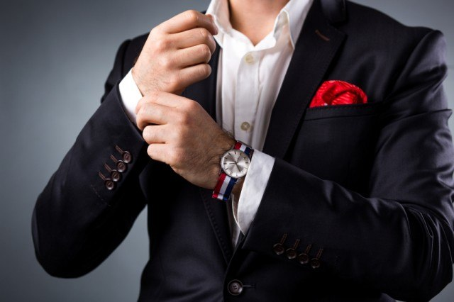 Man wearing a suit with a pocket square and watch