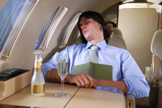 man sleeping on plane with a glass of Champagne in front of him