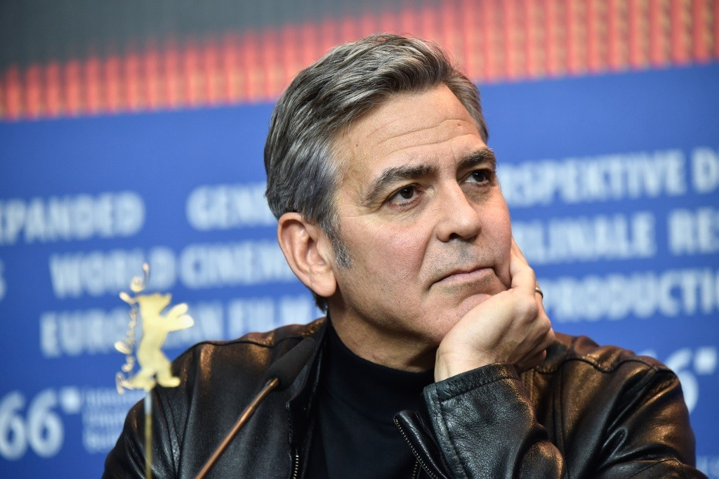 George Clooney resting his head on his hand.