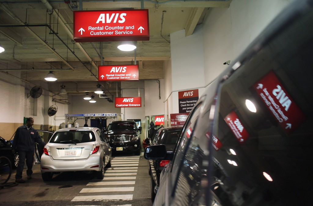 Cars sit in a lot at an Avis rental car branch