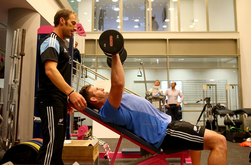 A trainer spots a man doing incline dumbbell presses
