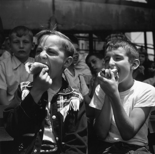 Two young boys eating hot dogs.