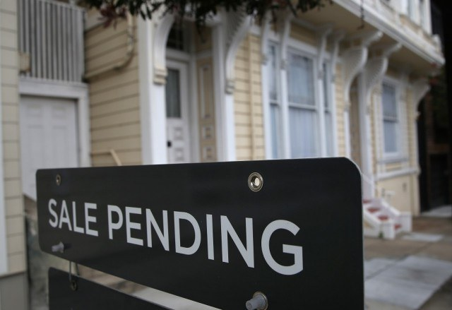 """A home with a sign in front of it saying """"Sale pending"""""""