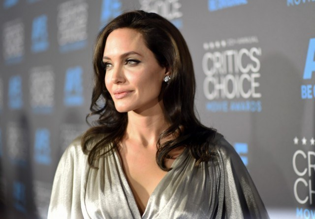 Angelina Jolie stands in a silver gown at the Critic's Choice Awards.