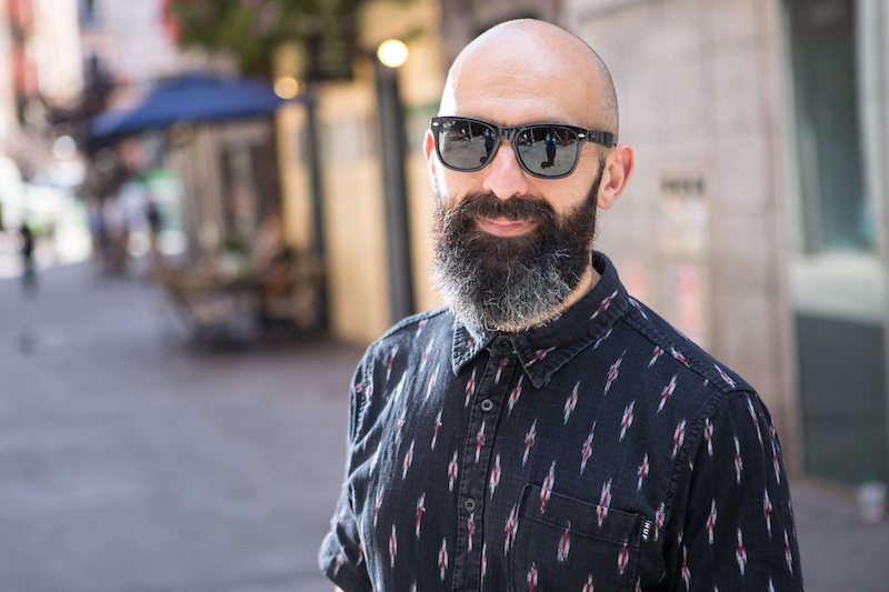 a trendy man wearing a button up shirt and sunglasses