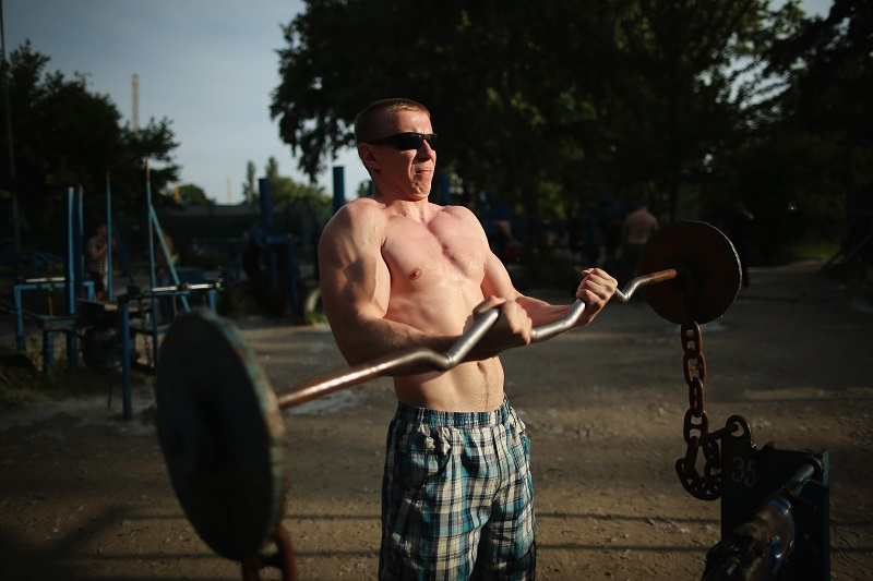 man lifting a heavy barbell outside