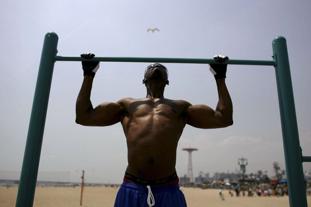 Man doing pull ups on the beach