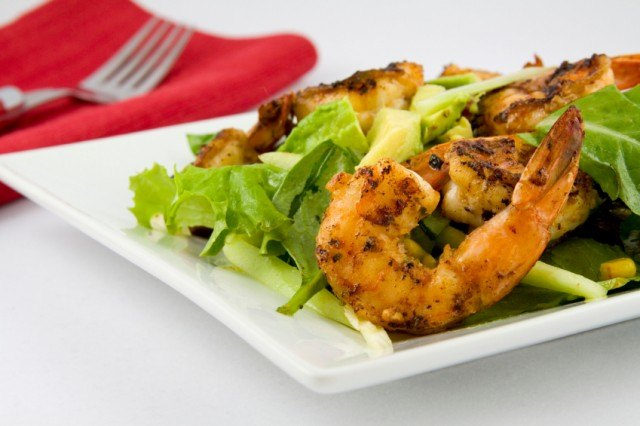 A salad complete with grilled shrimp and avocado
