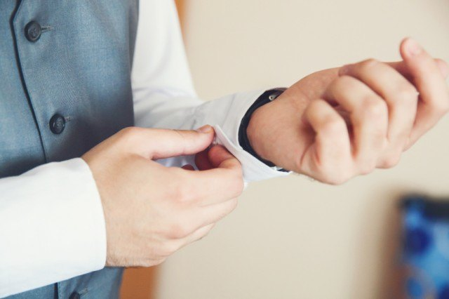 A groom tightening his cuff links.