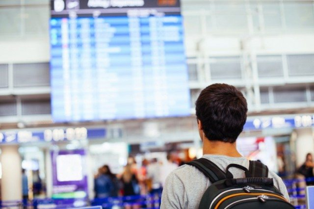 Man looking at the airline schedules at an airport