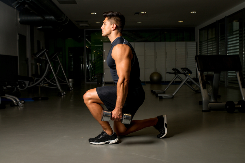 Man does weighted lunges at the gym