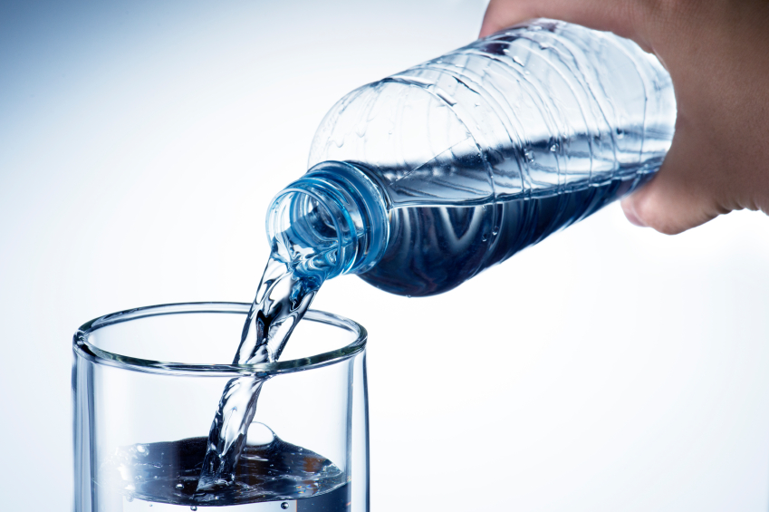 A hand pouring water from a plastic bottle into a glass.