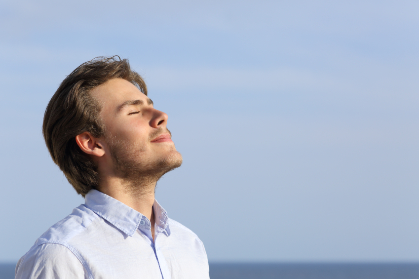 Relaxed man taking a deep breath
