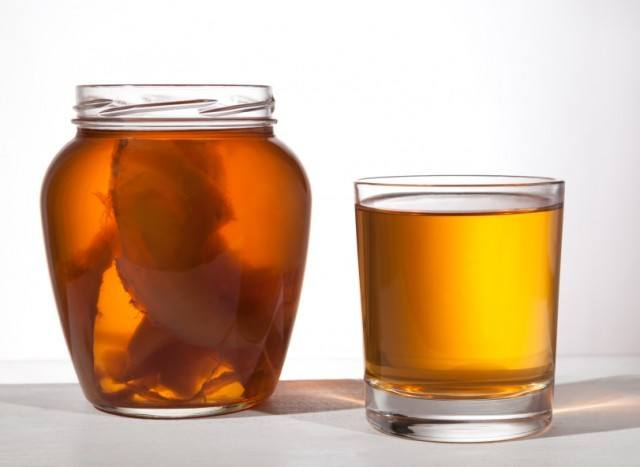 Jar and glass of kombucha in front of a white background.