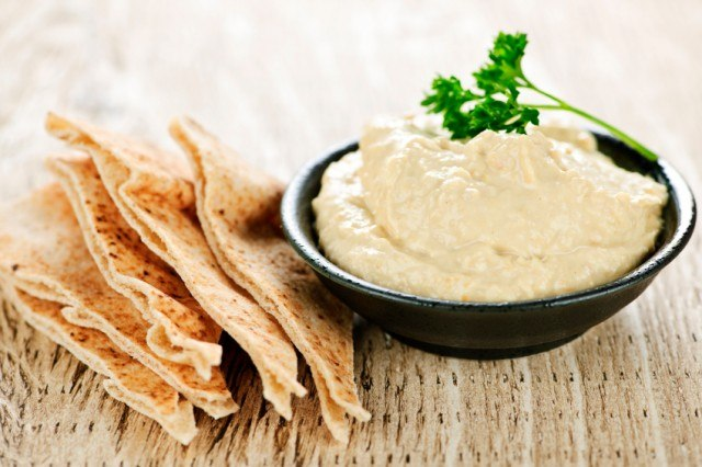 A bowl of hummus and sliced pita chips.
