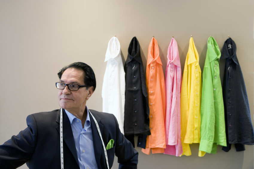 Male tailor by shirts hanging from wall, apparel, style