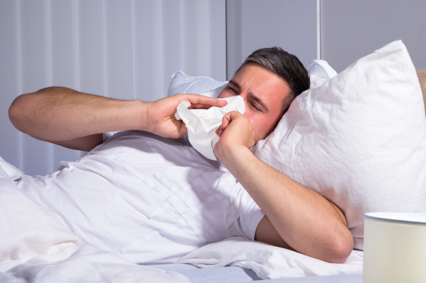 Man suffering from allergies, blowing nose