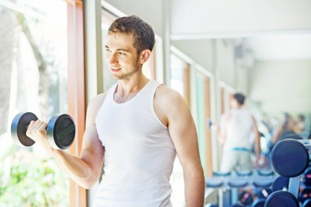 man lifting weights as he looks out the window