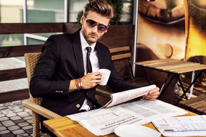 Man in a suit reading the newspaper