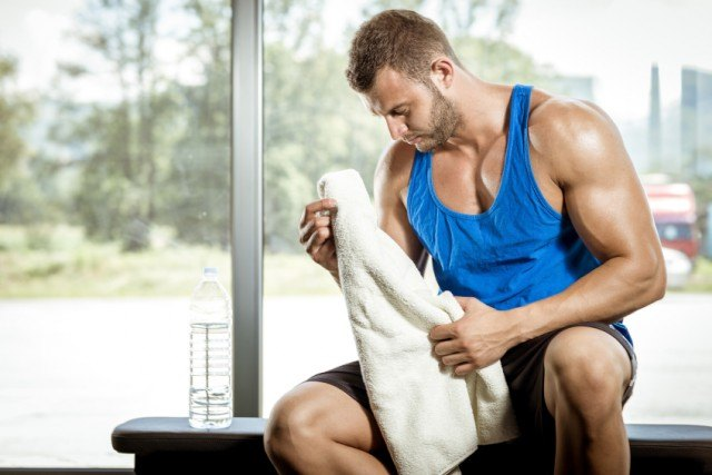 man sitting on a bench at the gym