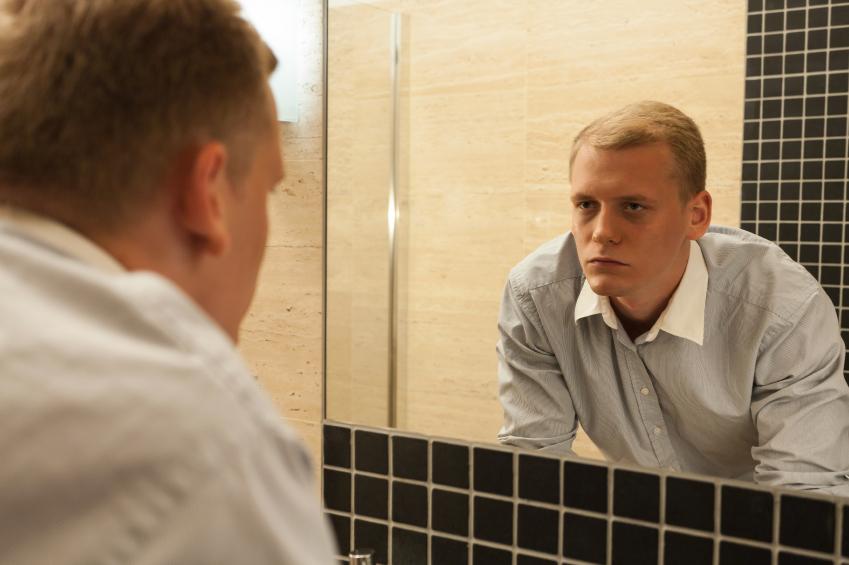 man looking at himself in mirror