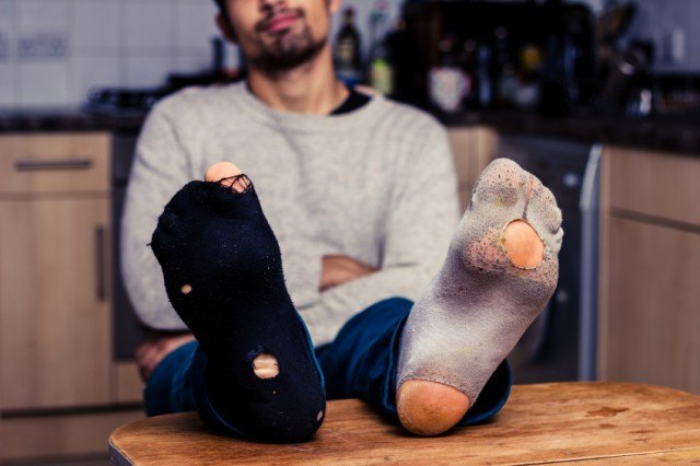 man with holes in socks