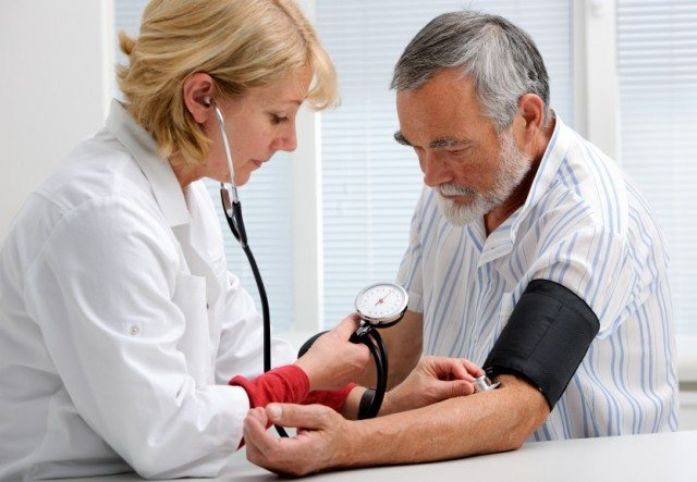 man getting his blood pressure taken by a doctor